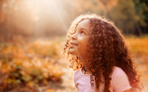 Afro american cute little girl with curly hair receives miracle sun rays from the sky